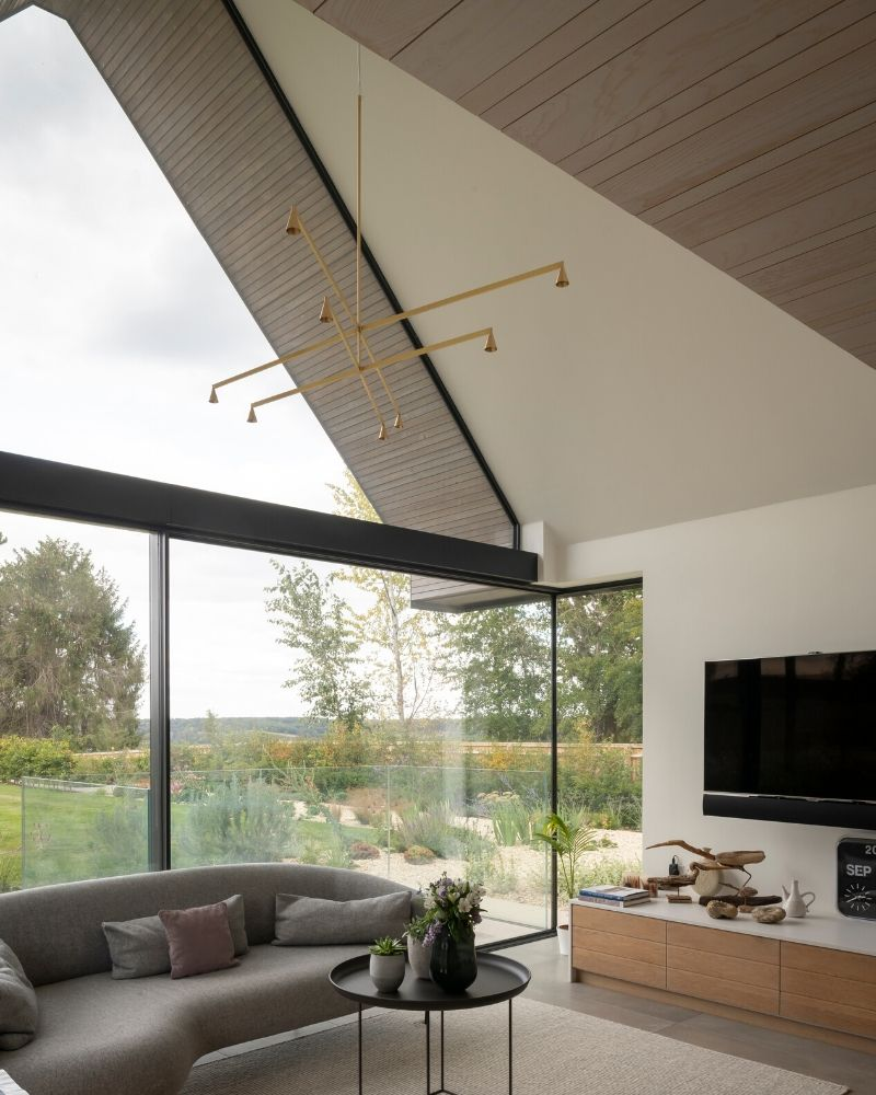 Frameless sliding glass doors integrated with large gable end glass window