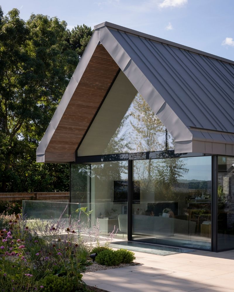 Frameless glass sliding doors integrated with fixed gable end window