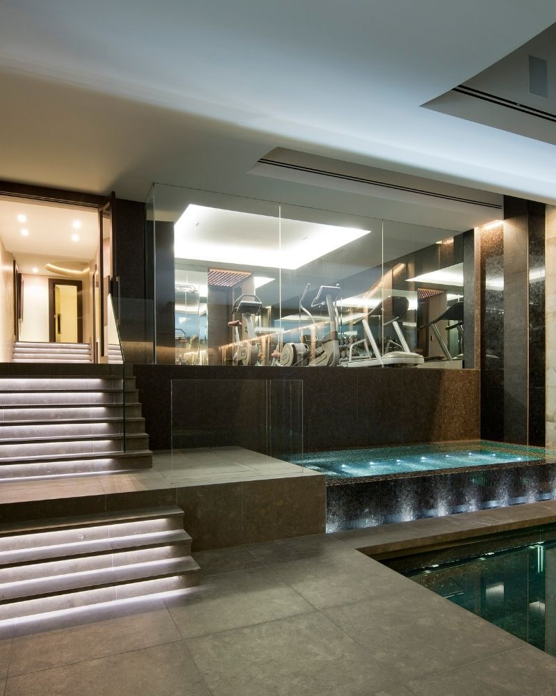 an internal glass wall between a gym and basement pool
