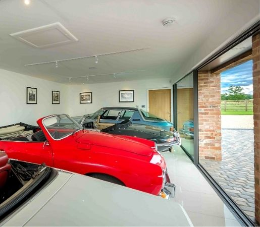 luxury car showroom garage in a barn conversion home with large sliding glass door